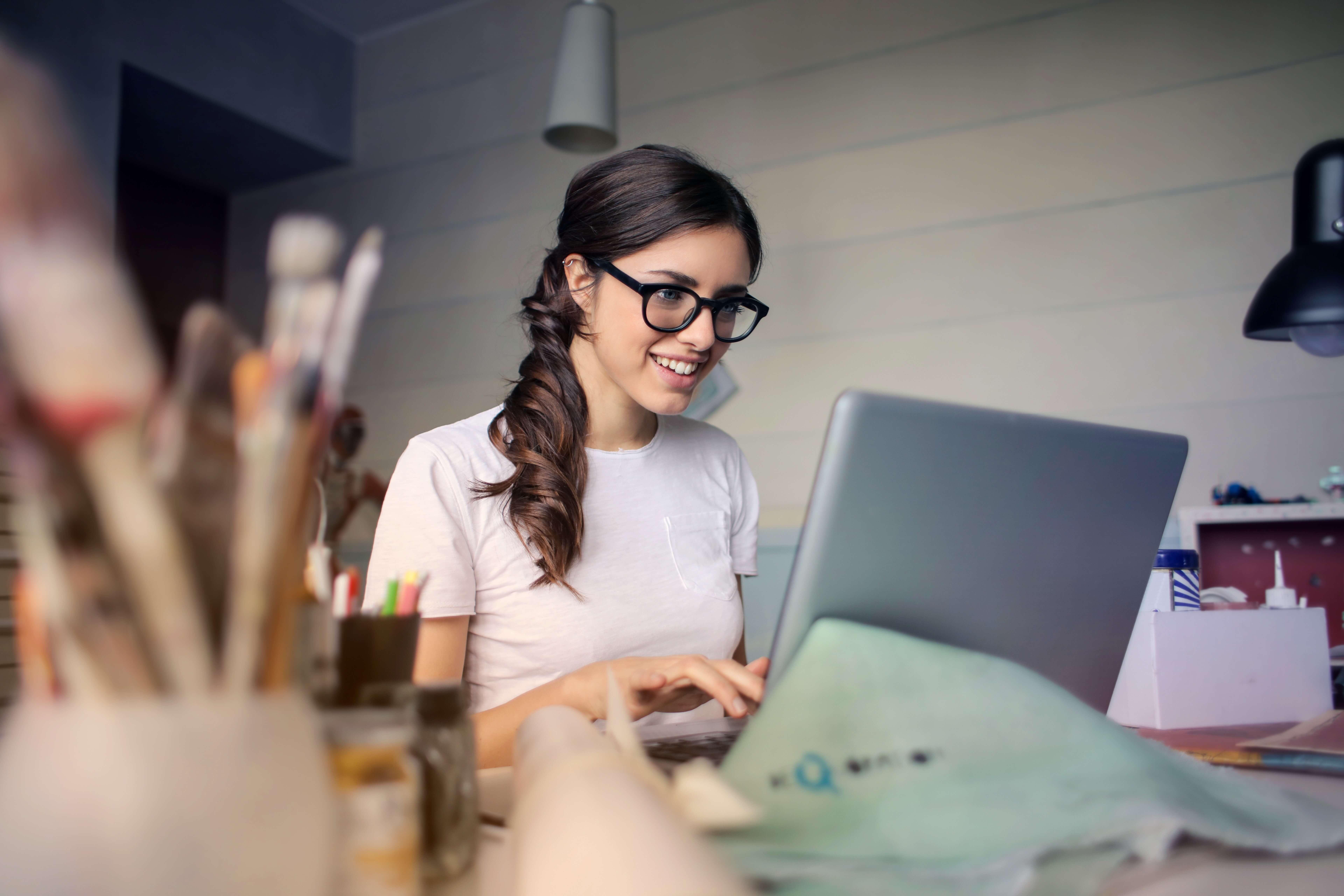 magen de joven fémina en área de trabajo escribiendo en una computadora portátil