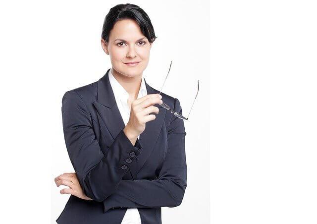 Imagen De Mujer Vestida Con Chaqueta Oscura Y Blusa Blanca, Tiene Espejuelos En La Mano