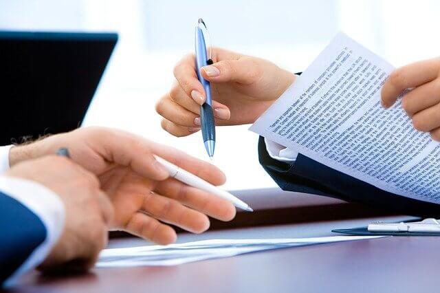Imagen que enfoca las manos de dos personas, una tine un bolígrafo azul en la mano derecha y un documento en la izquierda; el otro tiene un bolígrafo blanco en la mano izquierda señalando unos papeles sobre el escritorio.