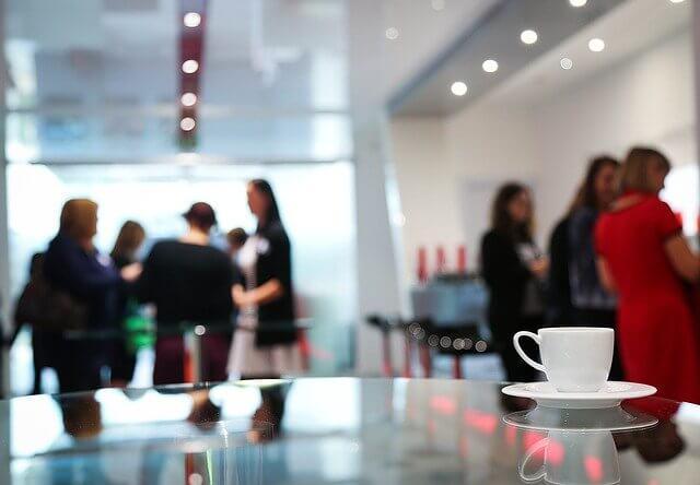 Imagen de una taza de café y en el fondo personas confraternizando.